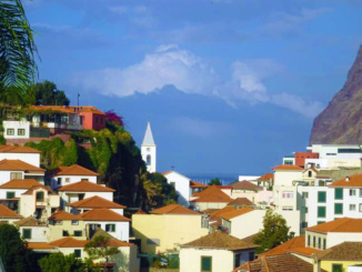 A view of the red roof buildings while driving through Funchal.