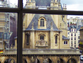 A cool view of the Reformed church in Paris looking out a window of the Louvre.
