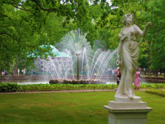 A modern fountain in the Park at Peterhof with the Aviary Pavilion in the background