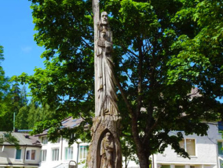 A tree carving depicting St Francis of Assisi outside the church