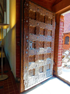 Another massive wood door with unique carvings and iron decor.